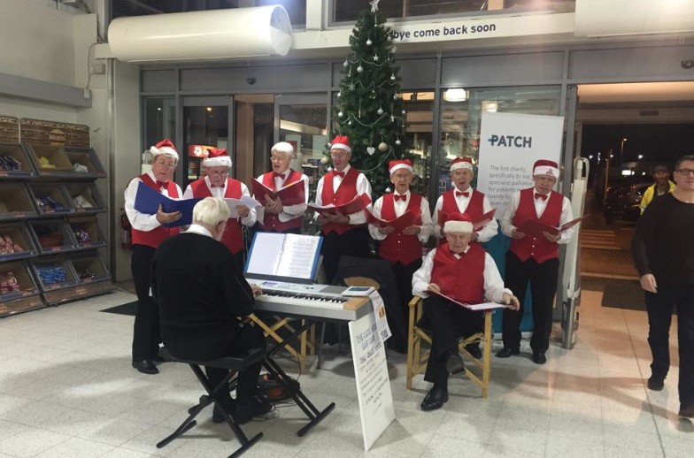 Norman (seated) with the choir in action. Margaret is not in the picture but is encouraging shoppers to fill her collecting bucket!